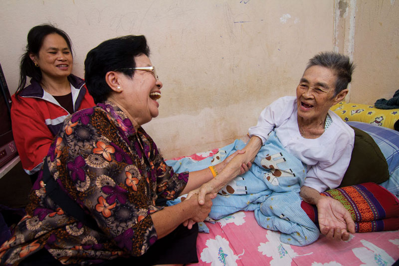 Community-based healthcare volunteer visits a housebound older woman as part of long-term care programme